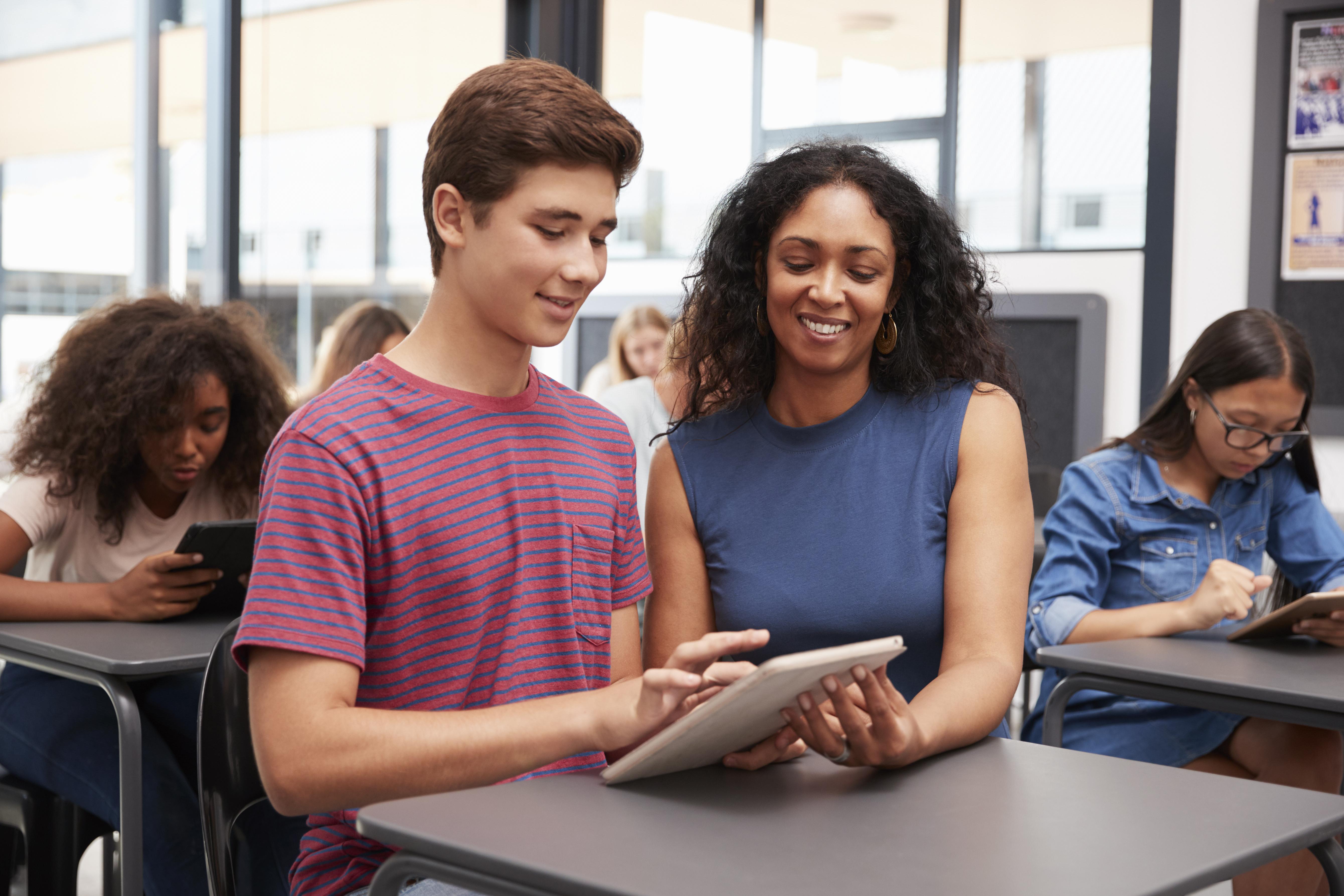 teacher-helping-teenage-schoolboy-with-tablet-P4AHJER.jpg